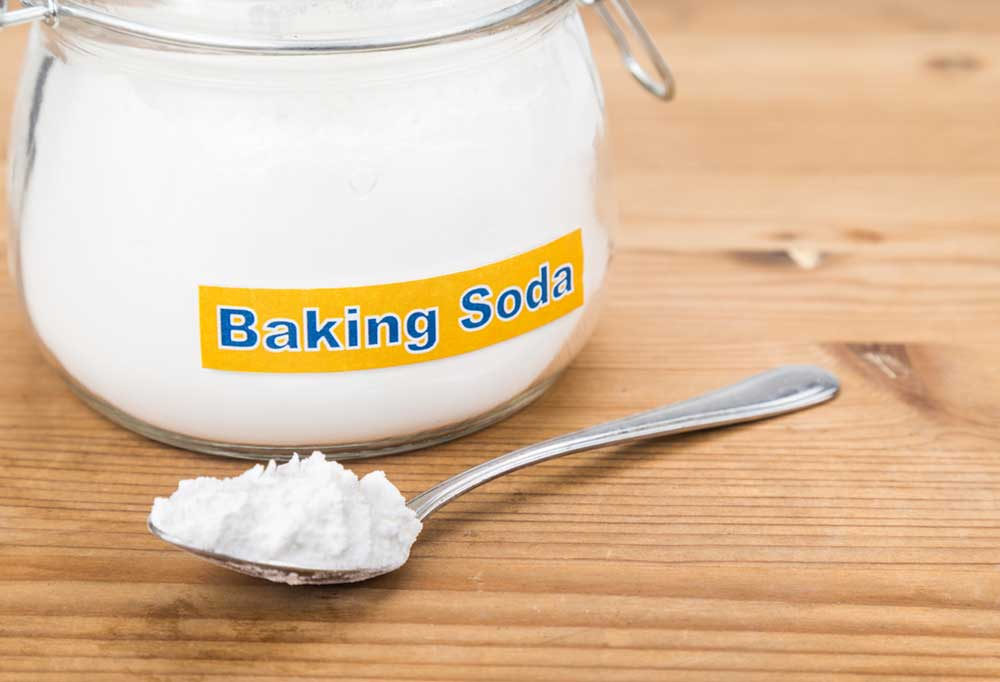 Spoon full of baking soda with a jar sitting next to it full of baking soda on a wooden surface