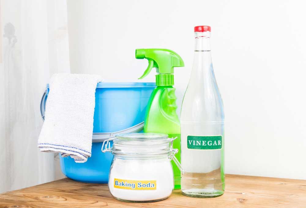 Bottle of vinegar, jar of baking soda, blue bucket and a green spray bottle on a wooden table.