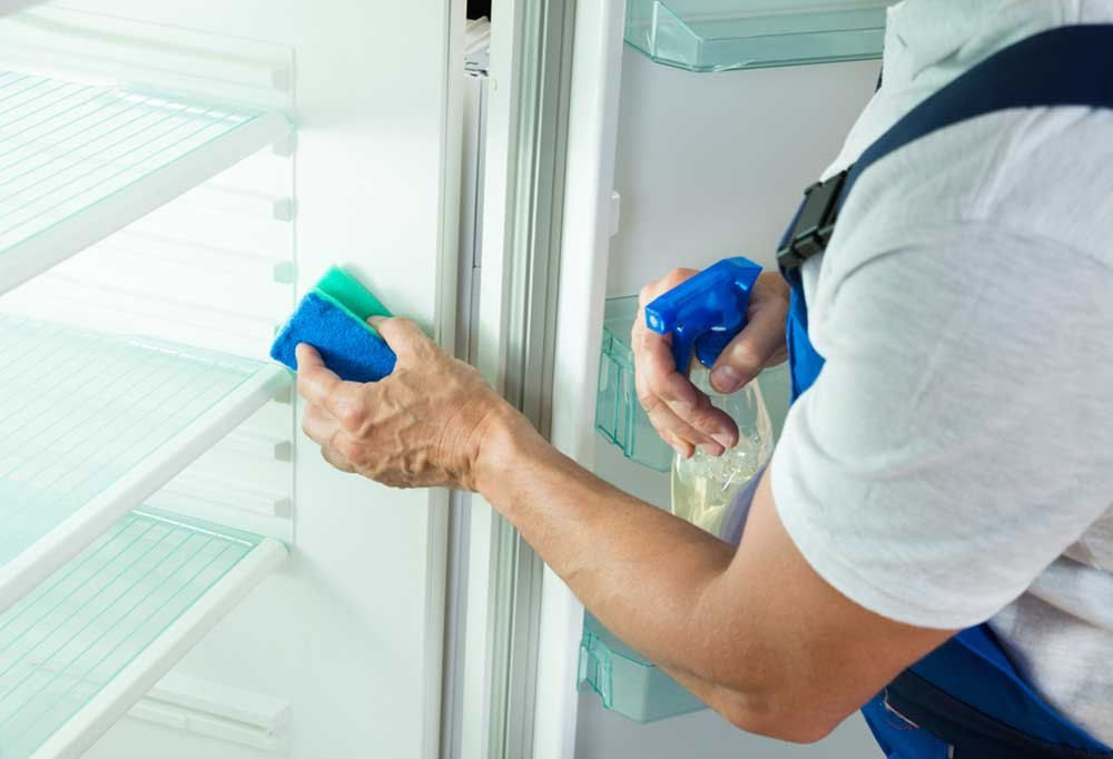 person cleaning the fridge with a blue sponge and spray bottle