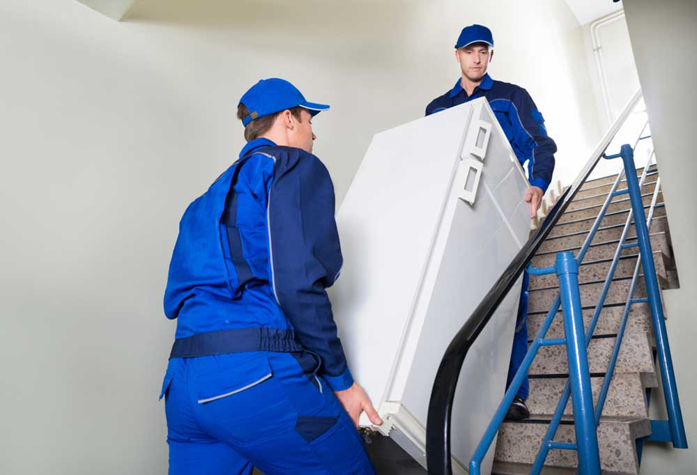 2 men in blue jumpsuits moving a refrigerator up stairs