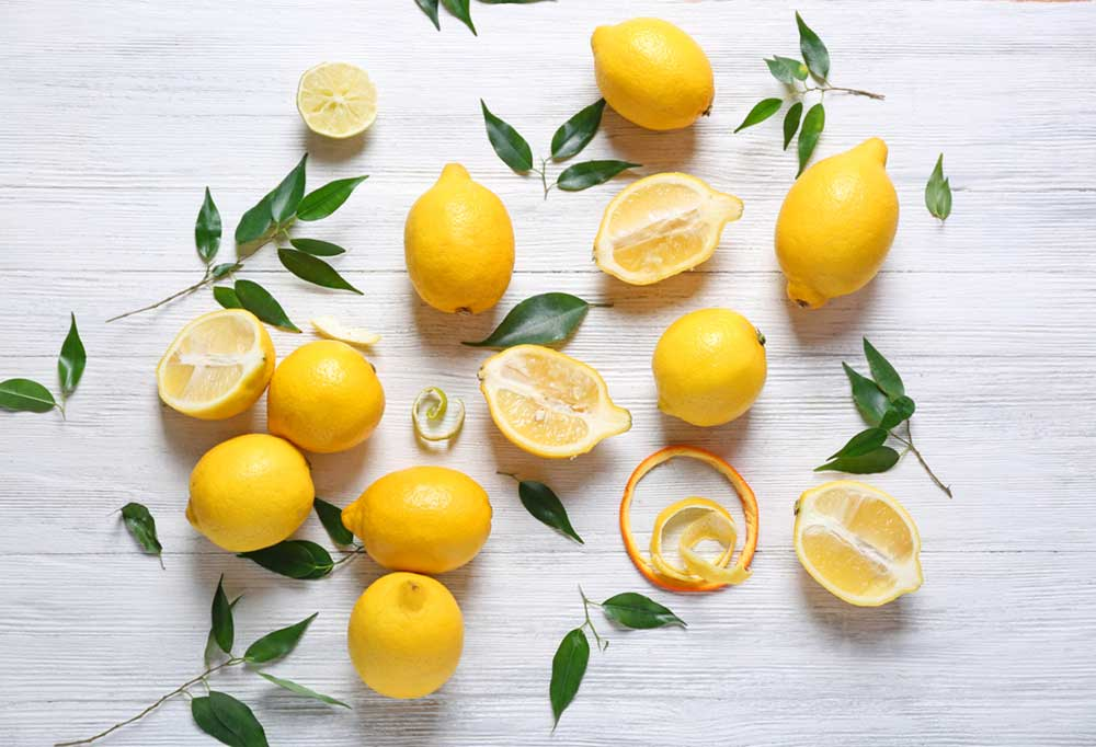 whole and cut lemons along with leaves and stems on a wooden surface