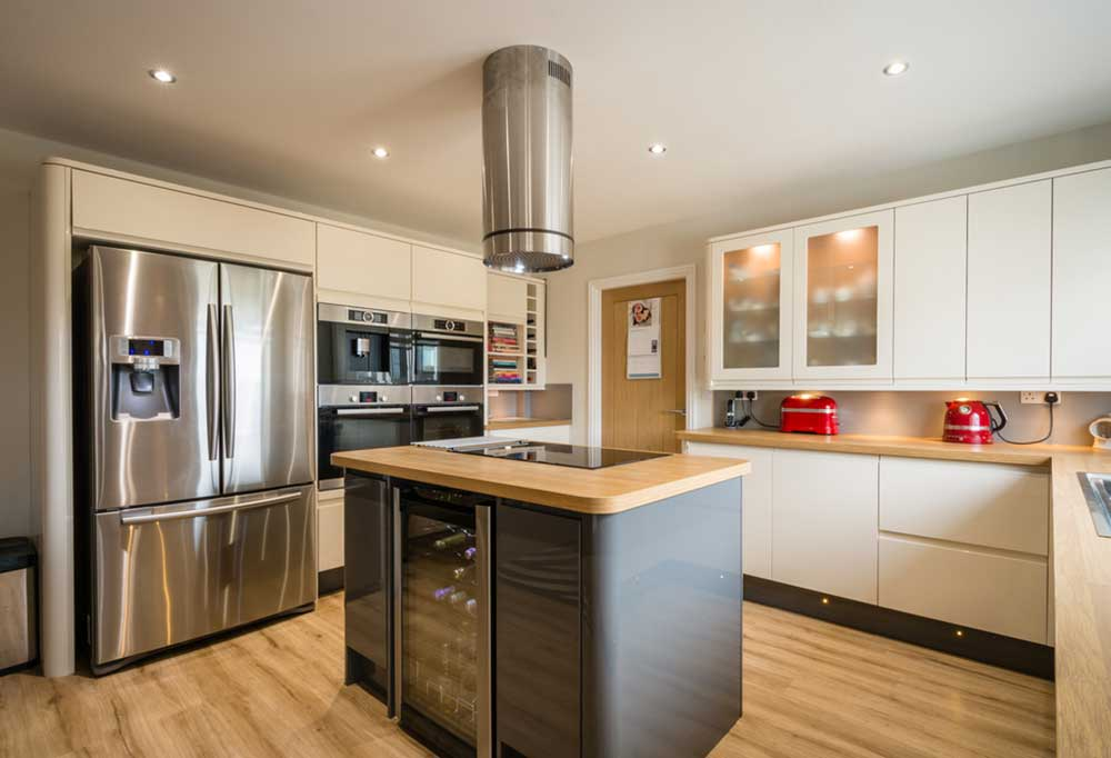 White cabinet kitchen with center island wine cabinet and stainless steel fridge