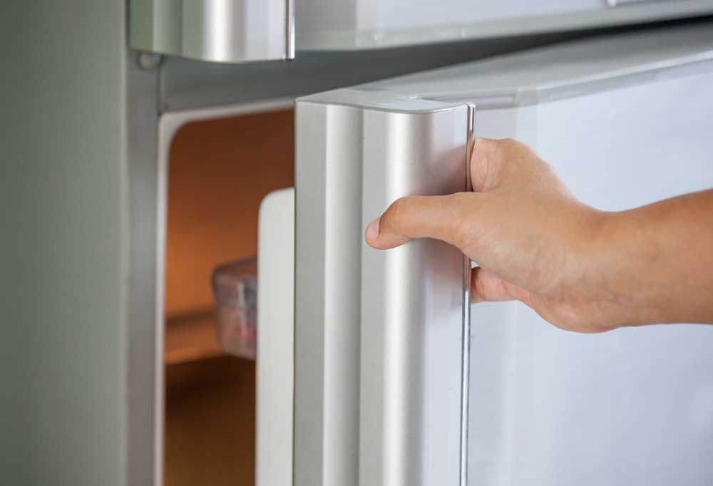 Hand opening a fridge door