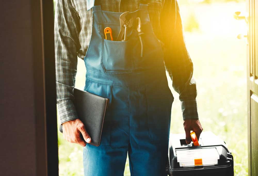 Handyman coming through a door with a notebook and toolbox