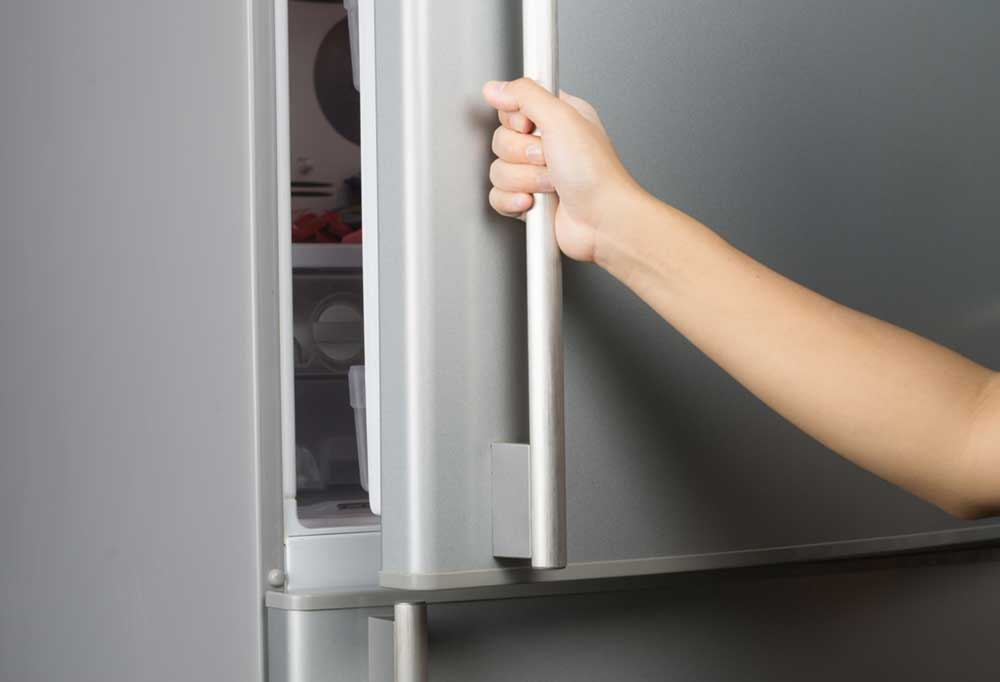 hand pulling open freezer by handle