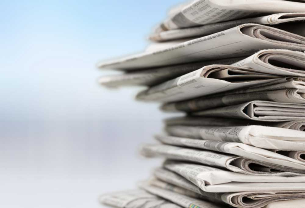 Stack of newspapers against a sky blue background