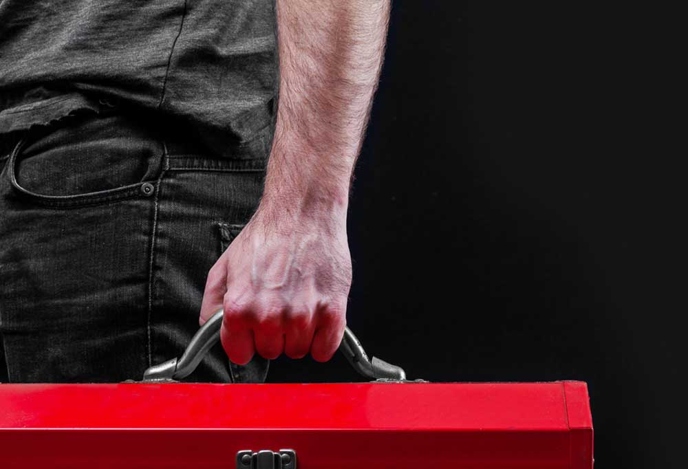male hand holding the handle of a red tool box