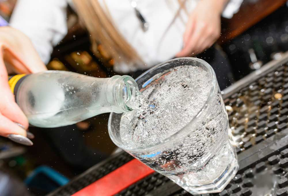 Bar tender pouring a bottle of club soda into a short glass