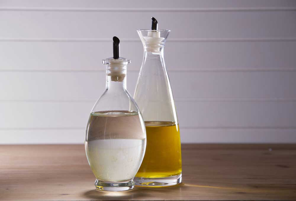 Vinegar and Olive Oil in bottles on a wooden table
