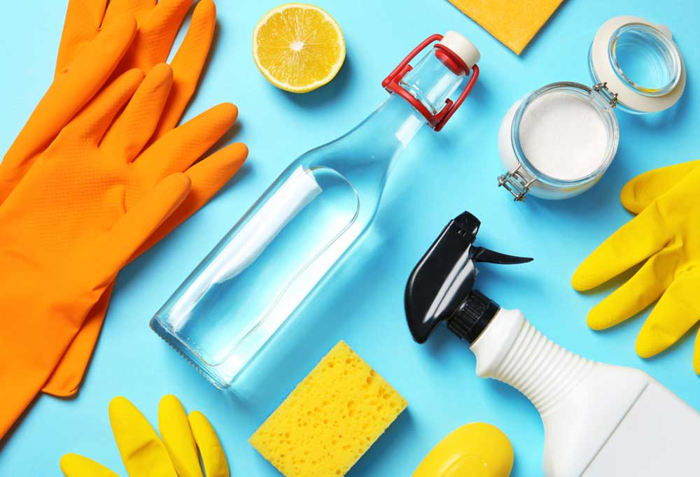 random cleaning supplies such as spray bottles and gloves laying on a blue background.