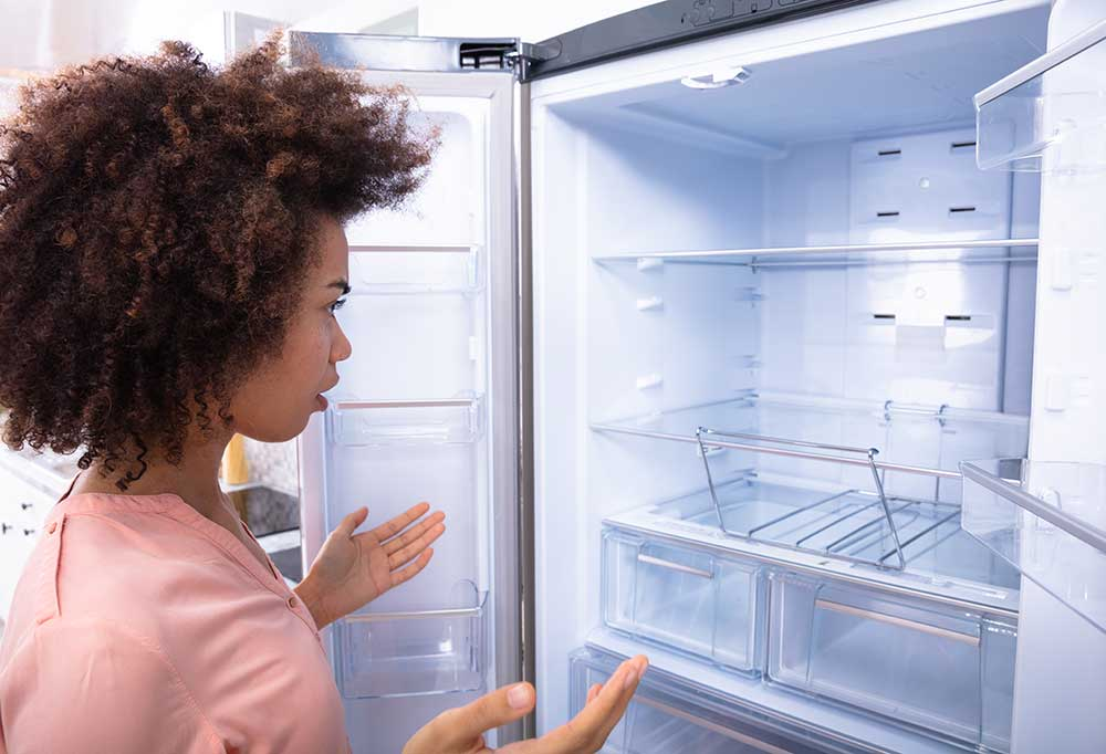 Woman staring inside fridge with hands out as if confused