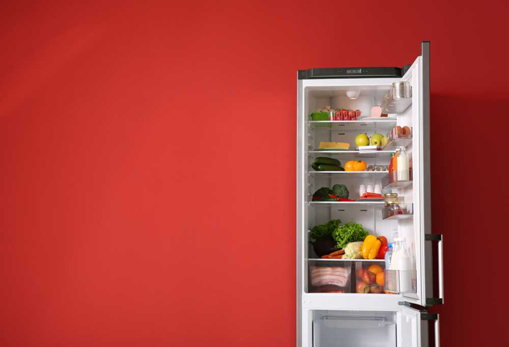 Open fridge filled with food open against a red wall