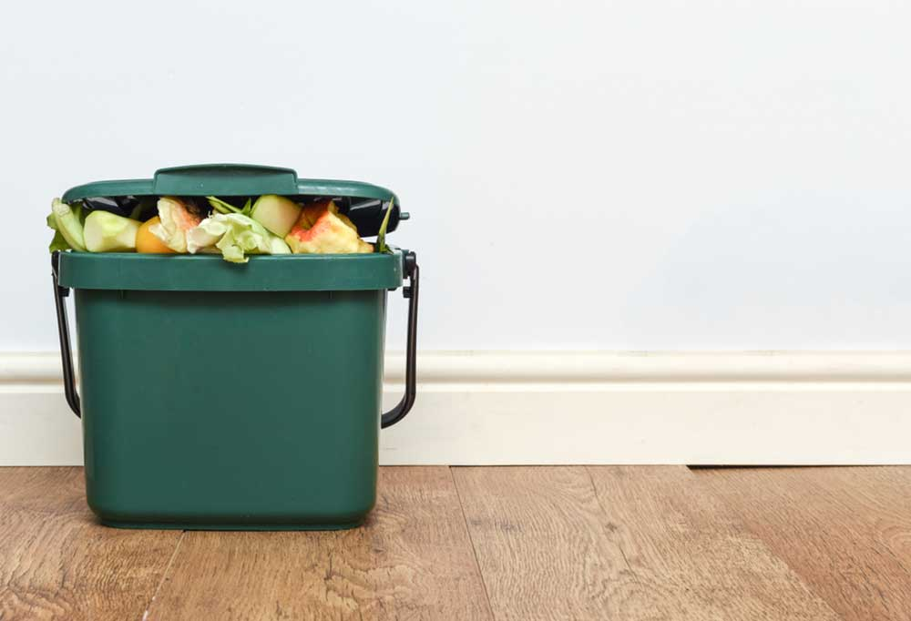 compost container full of thrown away food sitting on a hard wood floor