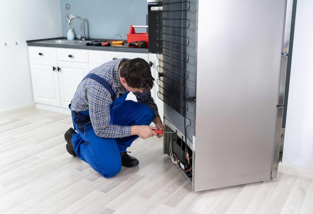 Repair man kneeling at back of fridge repairing it