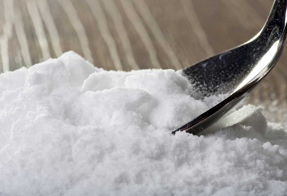 Pile of baking soda on a wooden surface with spoon dipped in