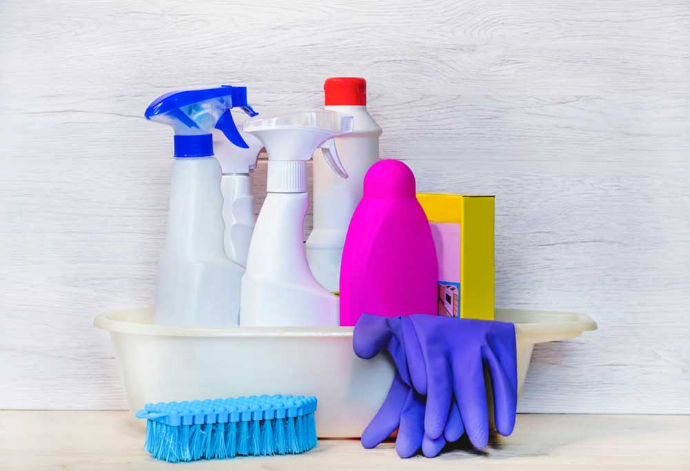 White bucket full of cleaning supplies, gloves, and a scrub brush