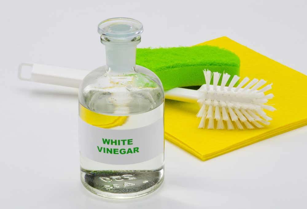 Vinegar in a glass bottle in front of a green sponge, white scrub brush, and yellow cleaning cloth