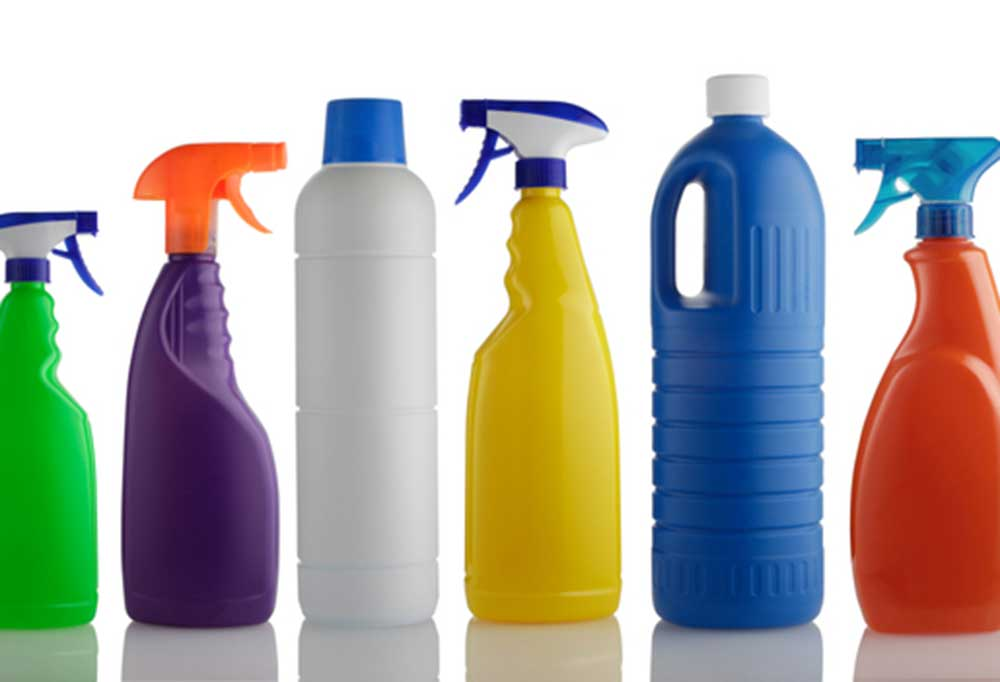 Variety of cleaning solution bottles on a white background