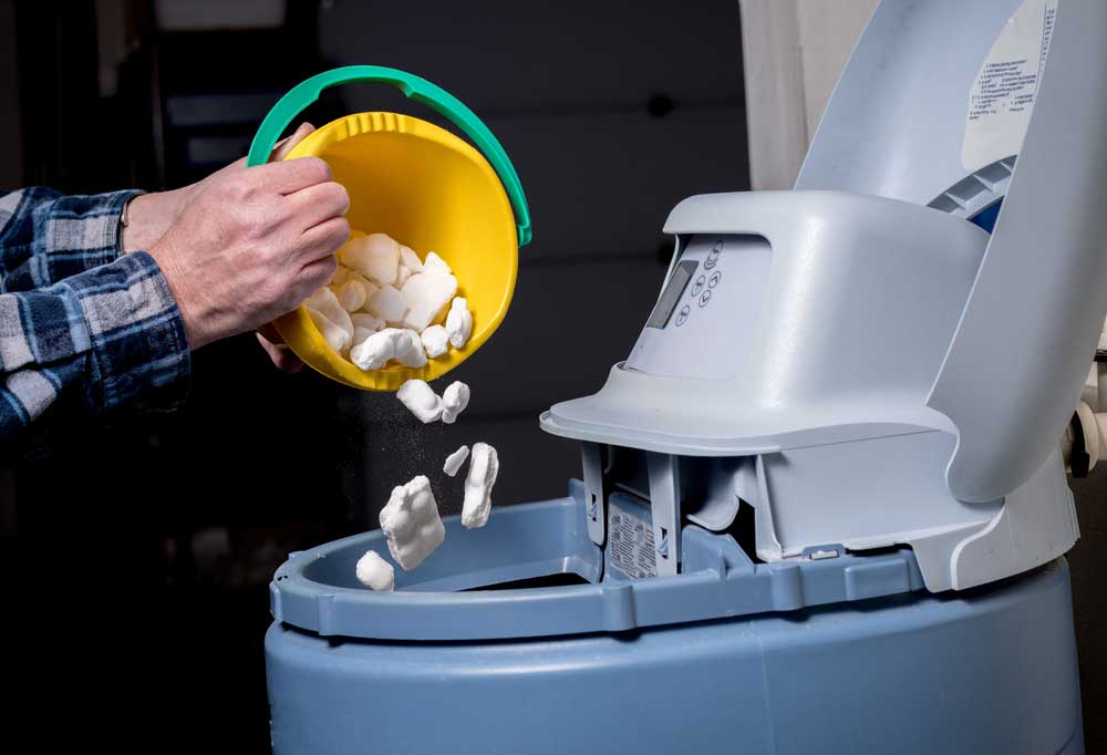 Salt being added by the bucket full to a water softener