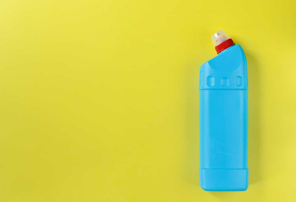 Blue and red cleaning solution bottle on a yellow background