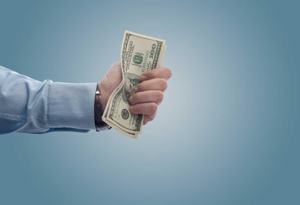 Hand holding hundred dollar bills on a blue background