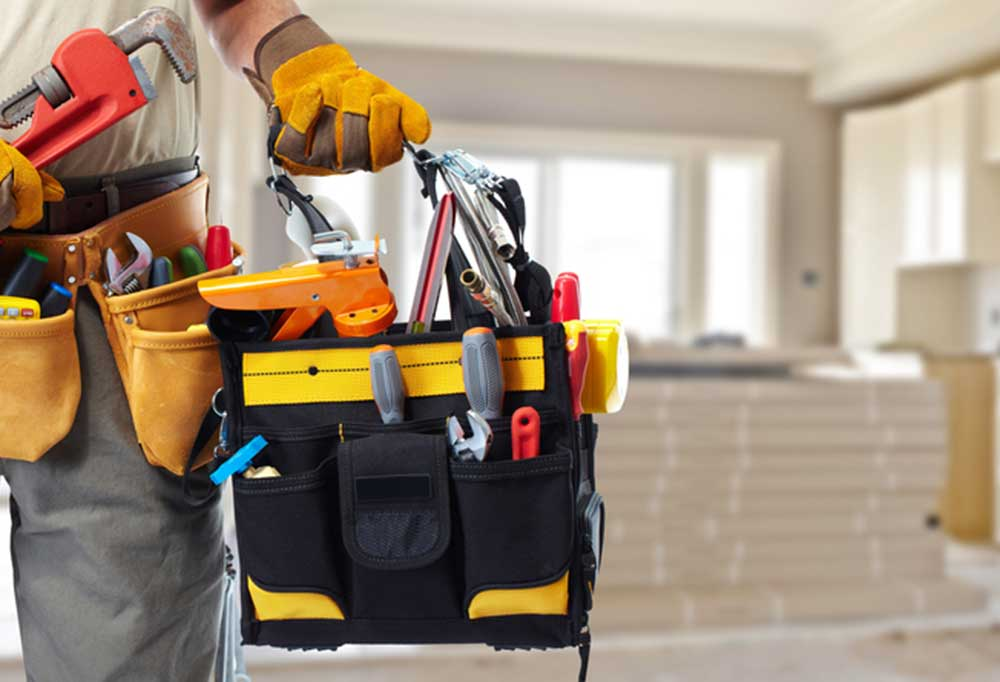 Handy man holding a full tool bag in one hand, wearing a tool belt, and holding pipe wrench in the other hand