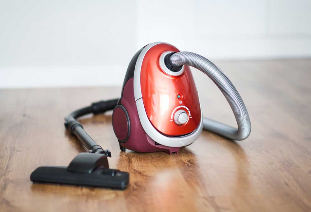 Small red vacuum cleaner sitting on hard wood floors