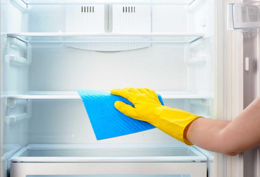 Yellow gloved hand drying fridge shelves with a blue towel