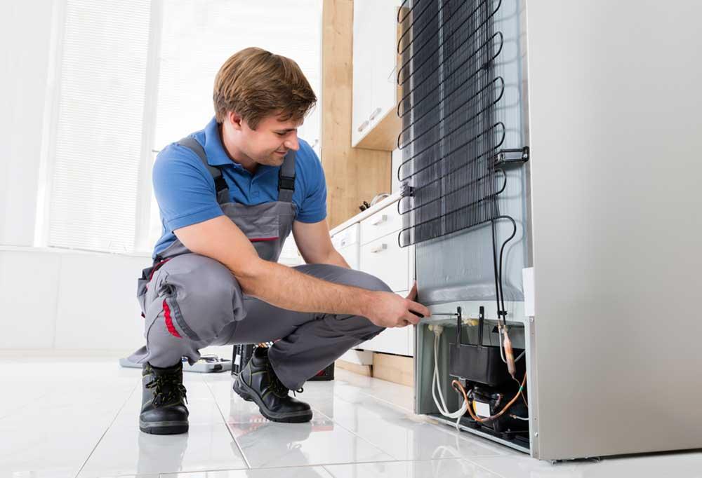 Repair man kneeling down at the back of a fridge repairing it.