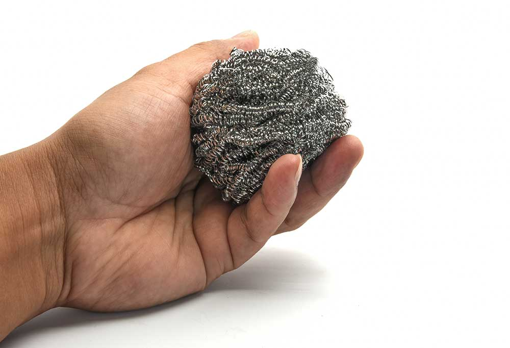 Hand holding steel wool on white background
