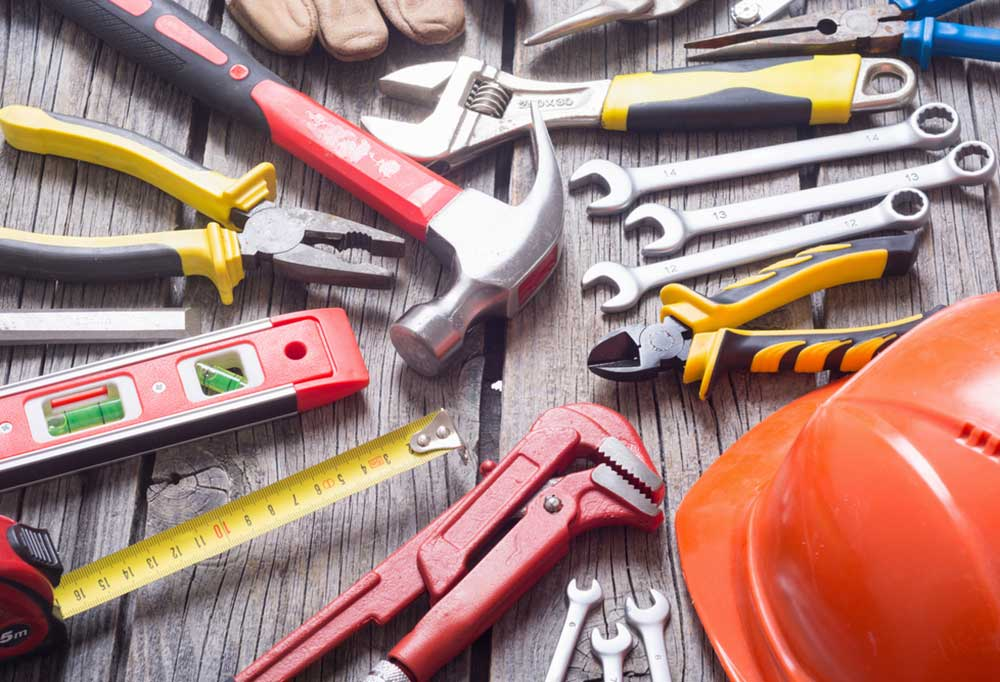 Variety of tools laid out across a wooden surface