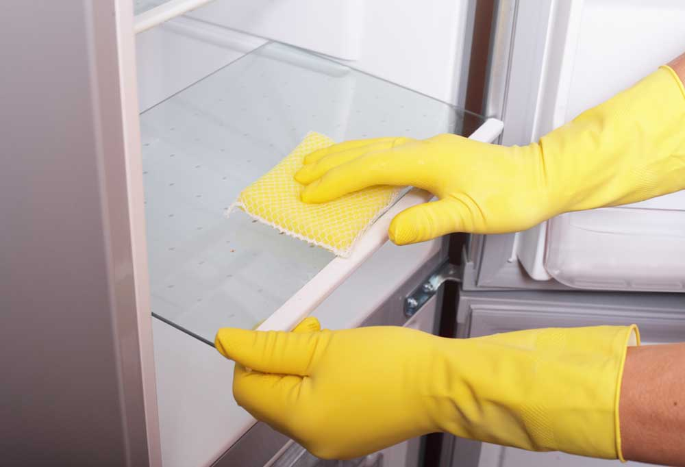 Yellow gloved hands with a sponge cleaning glass fridge shelves
