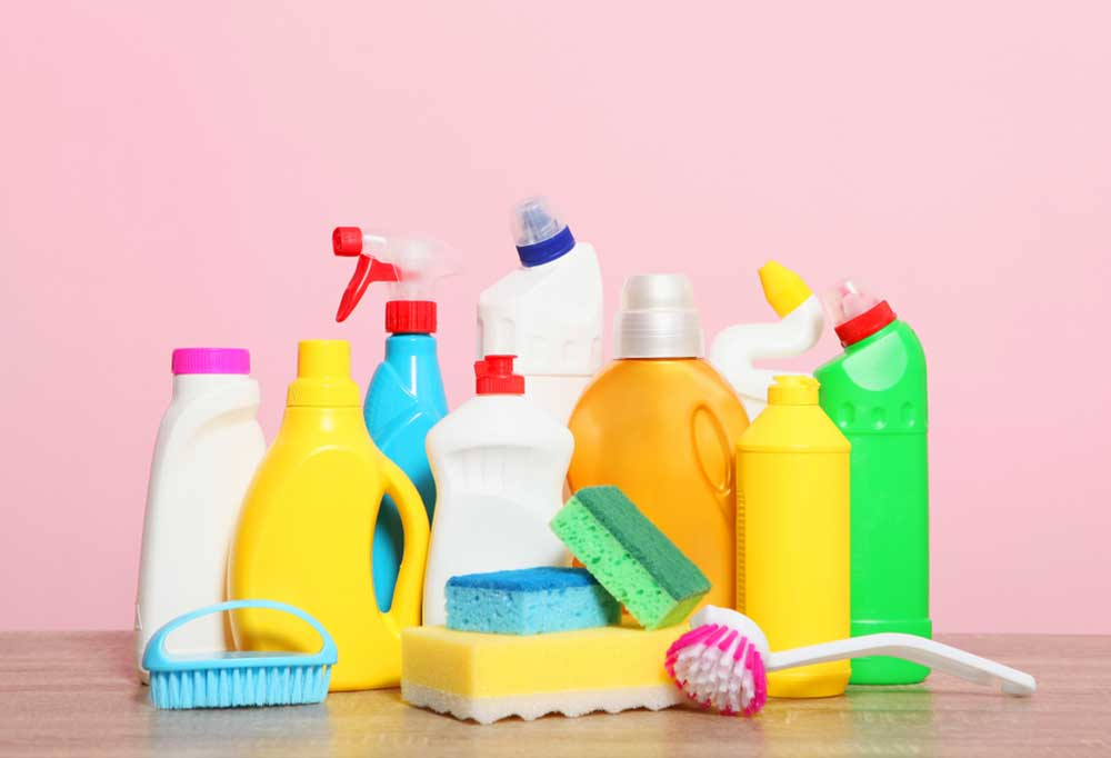 Variety of cleaning supplies on a countertop in front of a pink background