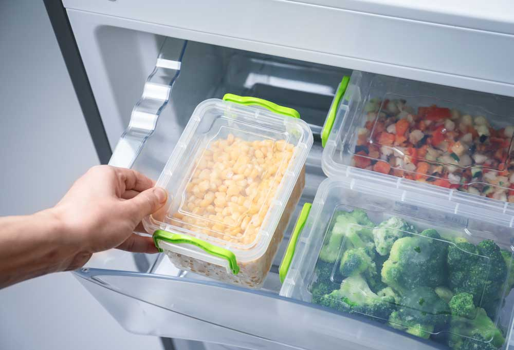 A hand reaching into a clear kitchen drawer to remove food storage containers of corn, broccoli, and mixed vegetables.