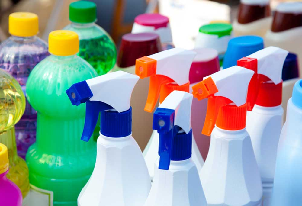 a variety of cleaning products in different colors in bottles and spray bottles.