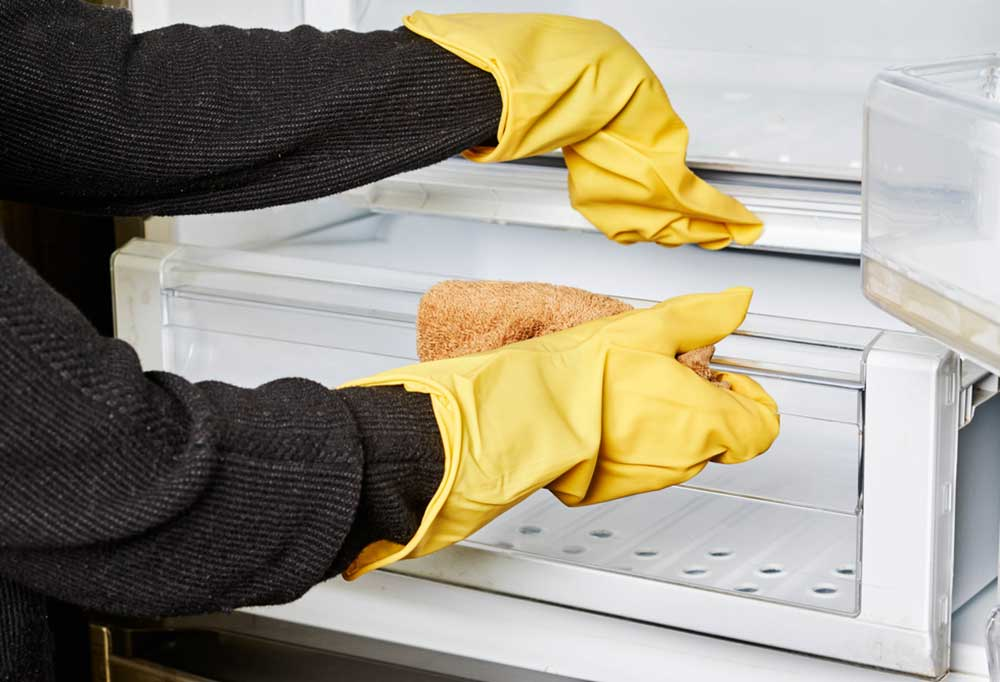Pair of hands in yellow gloves using a rag to clean crisper drawers in fridge