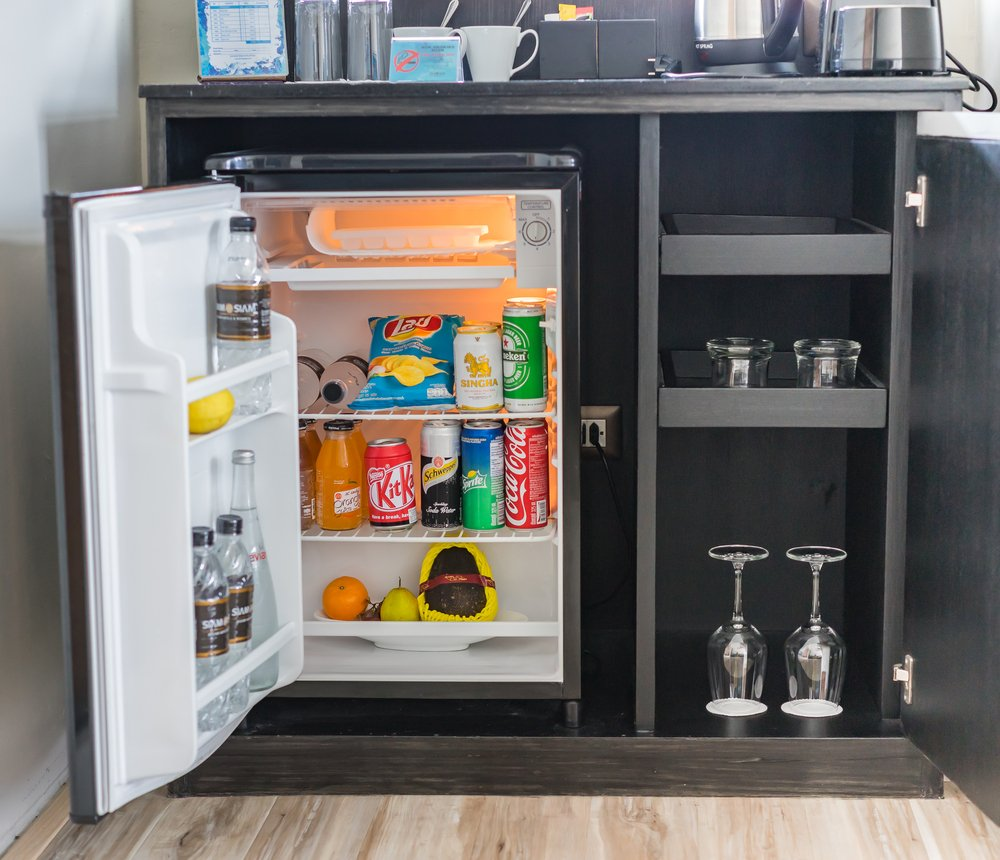Stocked mini fridge in small cabinet as if in a hotel room