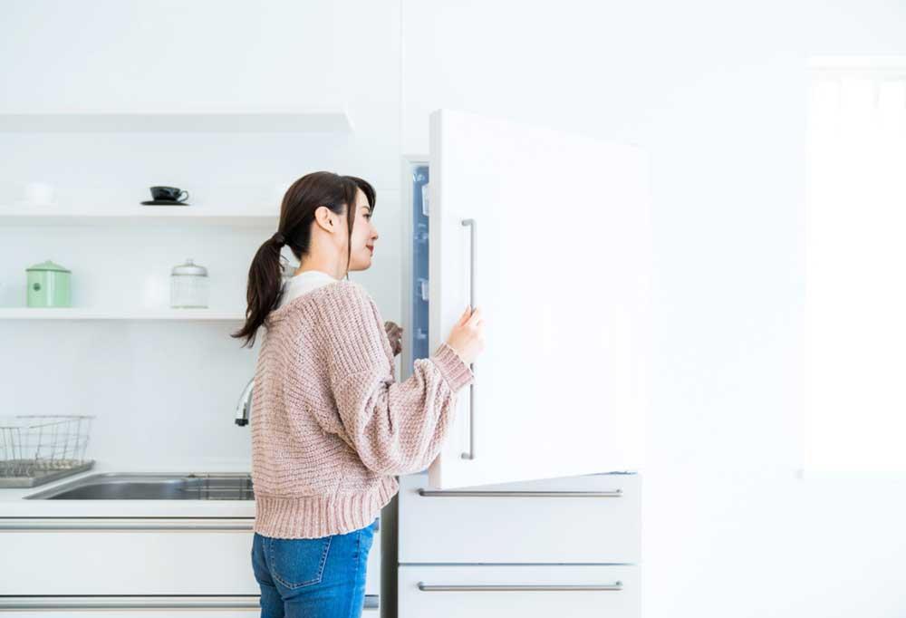 Woman peeking into a fridge door that is barely open