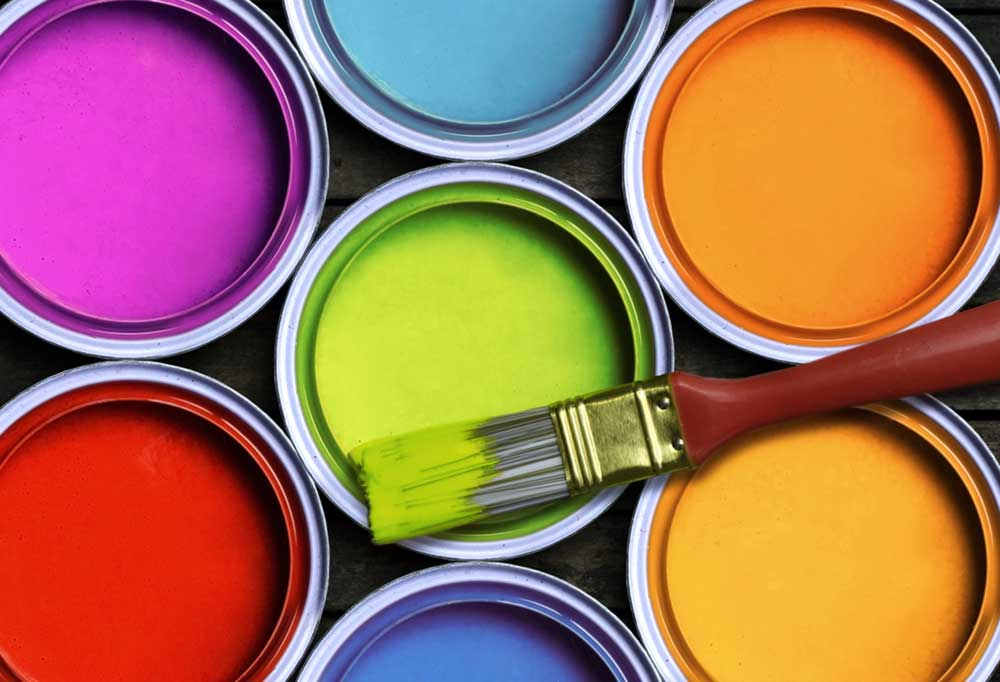 Top view of several open cans of brightly colored paint with a paint brush laying across the top