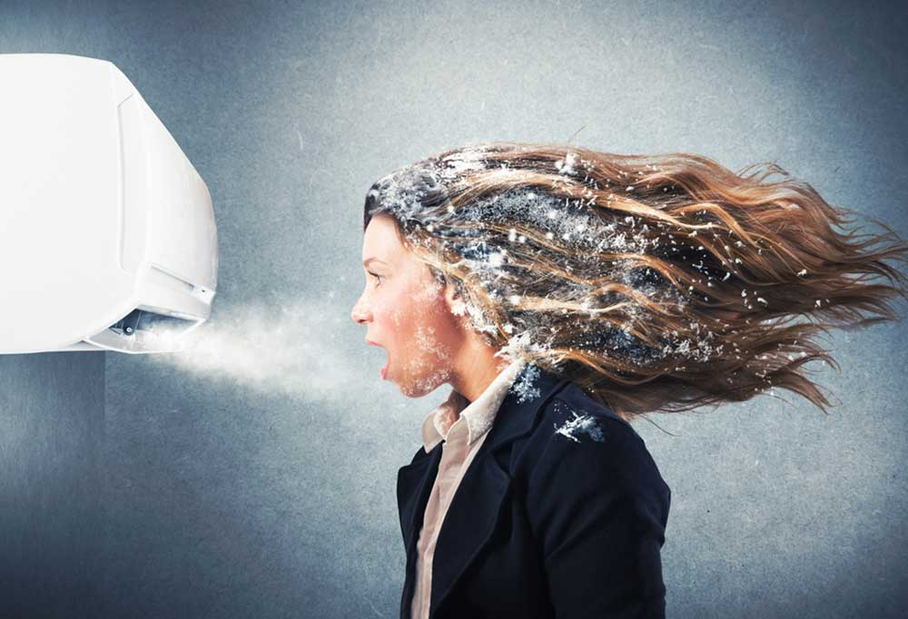 Woman with frost covered hair standing in front of an air conditioning wall unit