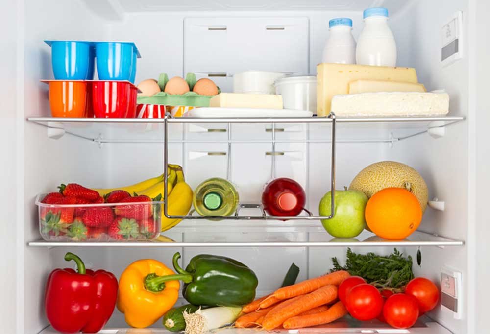 3 shelves in a fridge stocked with foods such as fruits and veggies, bottled drinks, milk, yogurts and cheeses.