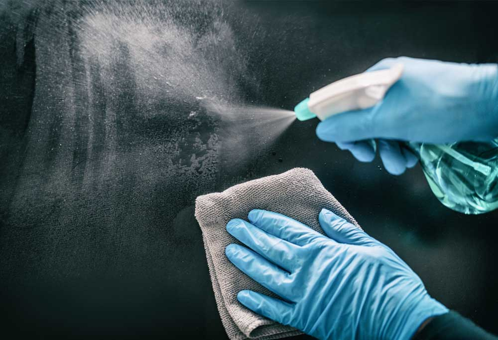 Set of hands with blue gloves spraying cleaner on dark glass and wiping it off with a grey cloth