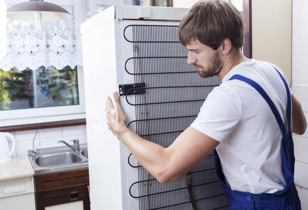 Man moving a white refrigerator