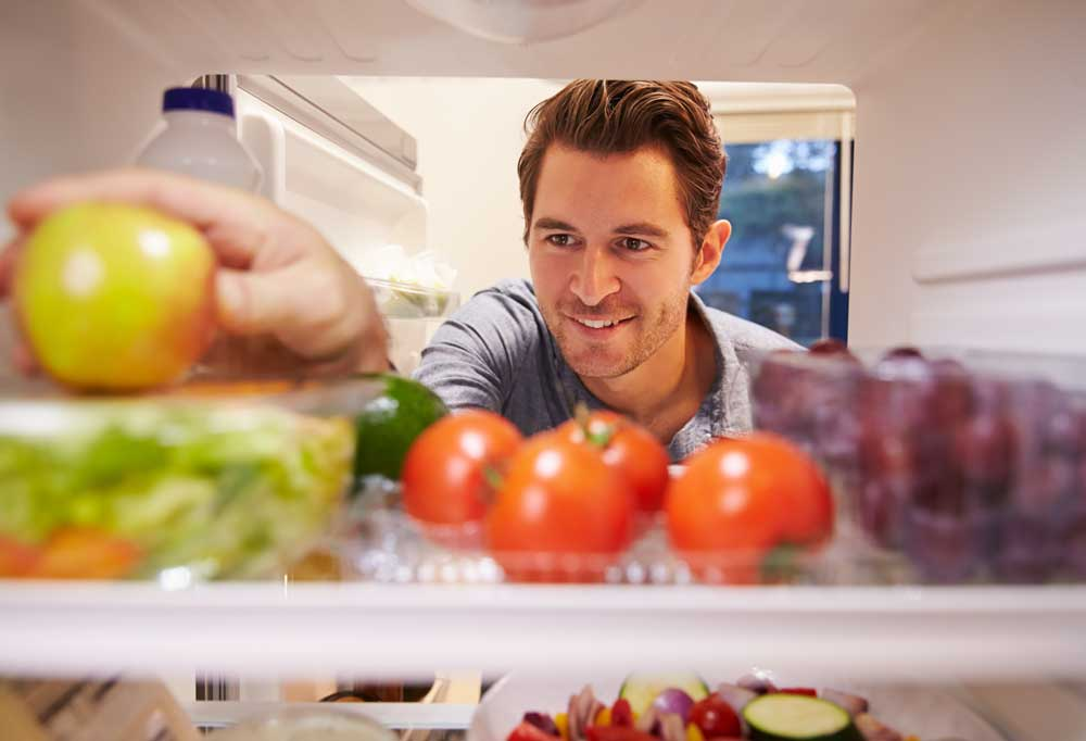 Man reaching into a fridge full of food for a vegetable.