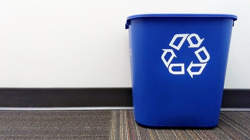 Blue recycling bin sitting on carpet against a white wall
