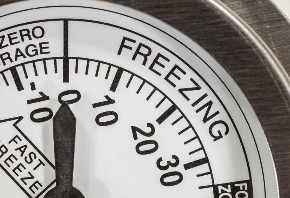 Close up of dial thermometer reading 0 degrees