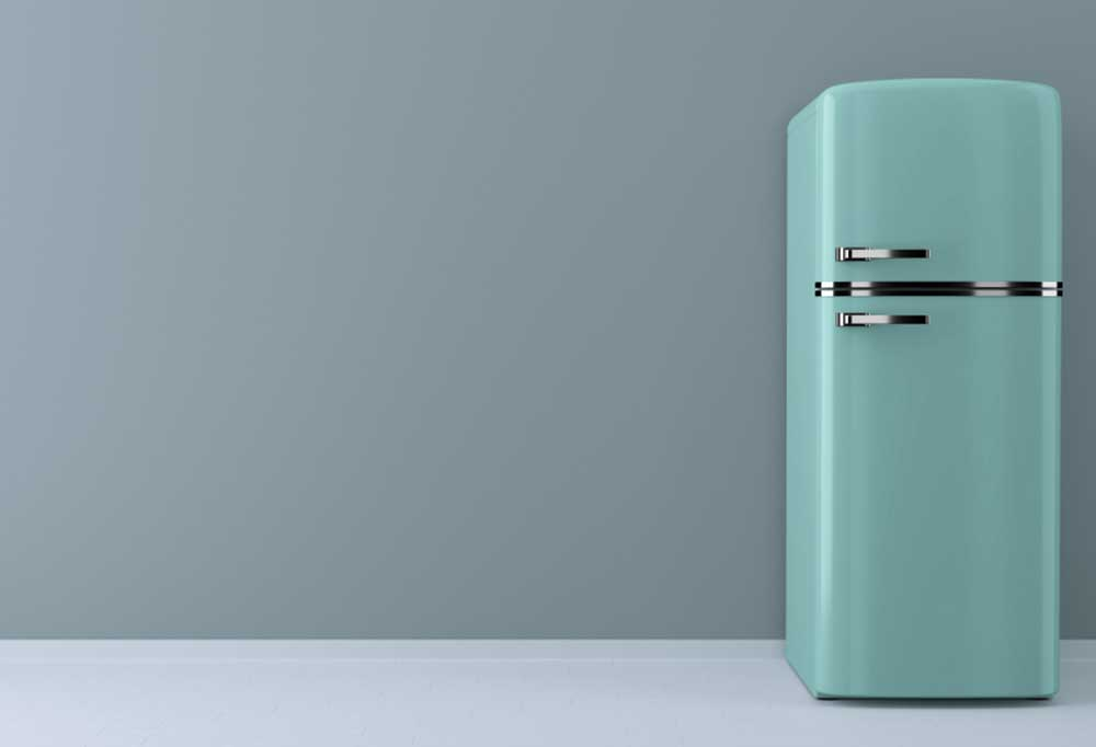 Teal colored fridge against a blue-grey wall