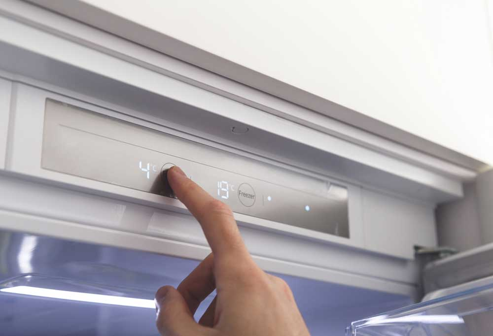 Finger pressing button on fridge controls to change temperature