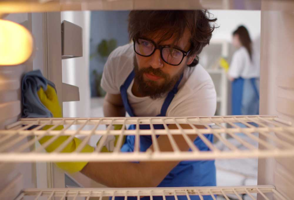 Inside the fridge view of a man with shaggy hair, a beard and mustache, and glasses, wearing yellow gloves while wiping down the inside of the fridge