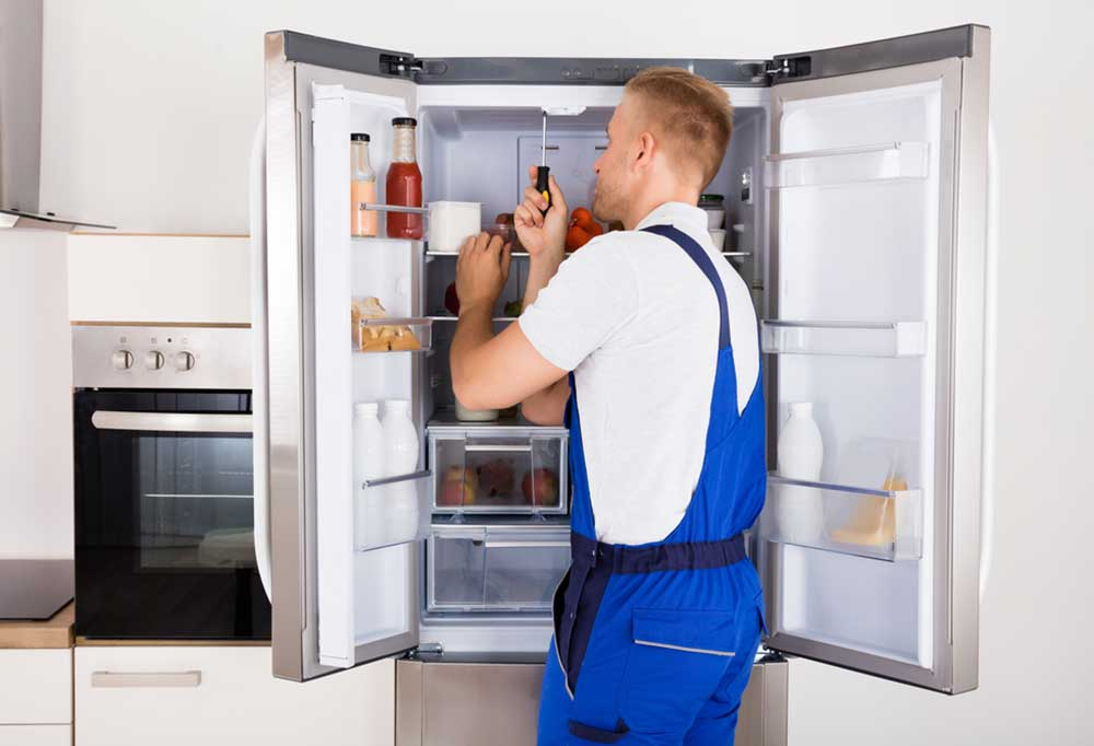 Man in blue jump suit with a screwdriver repair inside fridge with open side by side doors